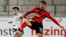 Gelandang Bayer Leverkusen, Nadiem Amiri, berebut bola dengan pemain Freigurg pada laga pekan ke-29 Bundesliga 2019/20 di Schwarzwald-Stadion, Sabtu (30/5/2020) dini hari WIB. Leverkusen menang 1-0 atas Freiburg. (AFP/Ronald Wittek/pool)