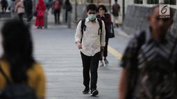 Seorang pria berjalan mengenakan masker pelindung untuk menghindari polusi udara buruk di Jakarta, Rabu (17/7/2019). Dinkes DKI menyarankan masyarakat untuk menggunakan masker saat beraktivitas untuk mencegah dampak polusi udara pada tubuh. (Liputan6.com/Faizal Fanani)