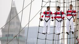 Tiga pelaut dari Angkatan Laut Peru berdiri di layar kapal saat mengikuti Parade Sail di Boston, AS (17/6). Dalam acara parade maritim ini diperkirakan 2 juta orang ikut berpartisipasi. (AP Photo / Michael Dwyer)