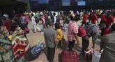 Orang-orang dengan masker berdiri dalam antrean untuk kereta api di Lokmanya Tilak Terminus, Mumbai, Minggu (11/4/2021). Para ahli di India meyakini perilaku menganggap remeh aturan jarak sosial serta mengenakan masker di ruang publik menjadi pola yang meningkatkan kasus COVID-19. (AP/Rafiq Maqbool)