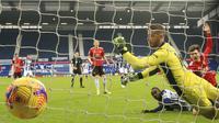 Penyerang West Brom, Mbaye Diagne, menyarangkan gol ke gawang Manchester United yang dijaga David de Gea pada lanjutan Liga Inggris 2020/2021, Minggu (14/2/2021) malam WIB. (Nick Potts/Pool Photo via AP)