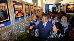 Ketua Umum Partai Demokrat, Susilo Bambang Yudhoyono (tengah) melihat pameran foto bertema kegiatan kader PD jelang puncak perayaan HUT Partai Demokrat ke-14 di Gedung Parlemen Senayan, Jakarta, Rabu (9/9/2015). (Liputan6.com/Helmi Fithriansyah)