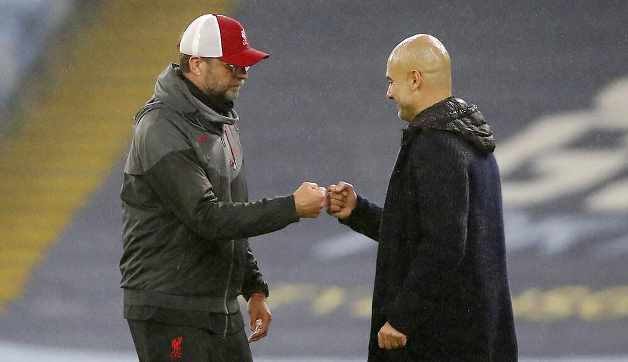 Pelatih Manchester City, Pep Guardiola dan pelatih Liverpool, Jurgen Klopp, saling menyapa pada laga Liga Inggris di Stadion Etihad, Minggu (8/11/2020). Kedua tim bermain imbang 1-1. (Martin Rickett/Pool via AP)