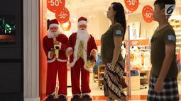 Pengunjung melintas di samping patung Santa Claus di Lippo Mal Puri, Jakarta, Jumat (22/12). Jelang Natal banyak pusat perbelanjaan mendekor bangunannya bernuansa natal untuk menarik daya tarik minat masyarakat. (Liputan6.com/Angga yuniar)