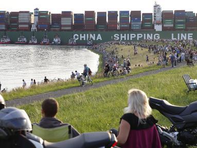 Sejumlah warga berkumpul di lokasi dimana kapal kontainer CSCL Jupiter Hong Kong terdampar di muara Westerschelde di dekat kota Bath di Belanda setelah insiden grounding (14/8).  (AFP PHOTO/Belga/Kristof Van Accom/Belgium Out)
