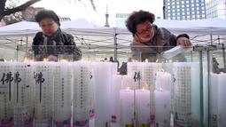 Dua orang wanita menyalakan lilin untuk mendoakan keberhasilan anak dan kerabatnya dalam mengikuti tes kemampuan Skolastik College tahunan di Seoul (23/11). Para ibu ini mengunjungi kuil Buddha Jogye untuk mendoakan anak mereka. (AFP Photo/Jung Yeon-Je)