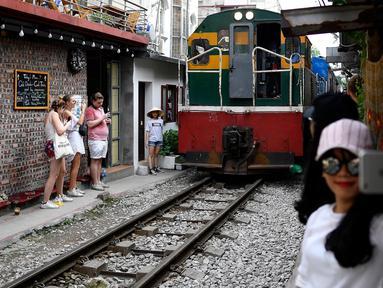 Foto pada 8 Juni 2019 menunjukkan seorang wanita berswafoto saat sebuah kereta melintasi jalur kereta api populer di Hanoi. Di ibu kota Vietnam tersebut rel-rel kereta yang berada di permukiman padat penduduk dijadikan destinasi wisata selfie. (Photo by Manan VATSYAYANA / AFP)
