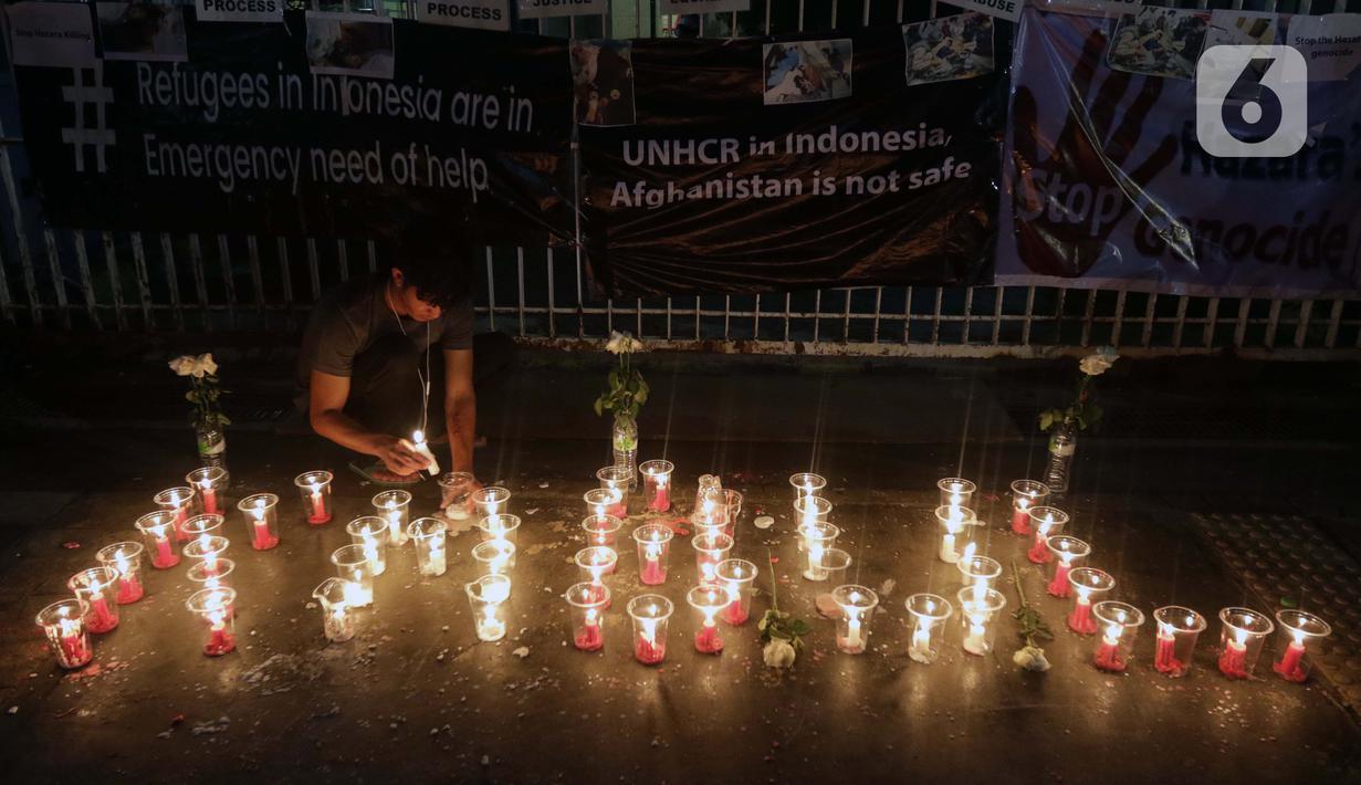 Seorang pencari suaka menyalakan lilin membentuk nama kota di Afghanistan saat aksi keprihatinan yang digelar di depan kantor UNHCR, Jakarta, Selasa (11/5/2021). Mereka prihatin atas peristiwa serangan bom yang menewaskan puluhan siswi di Kabul, Afghanistan. (Liputan6.com/Helmi Fithriansyah)