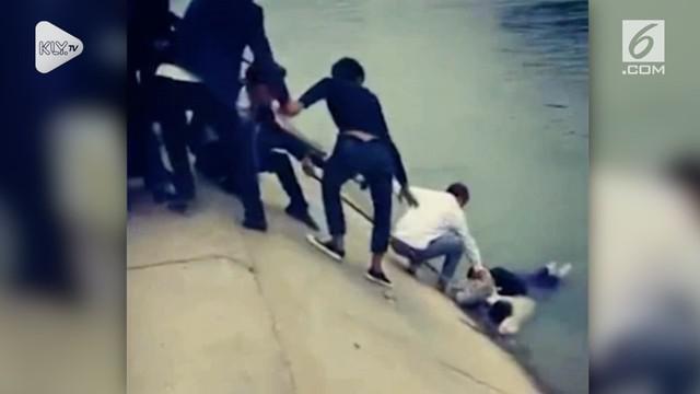 Belasan pejalan kaki berhasil menyelamatkan seorang gadis yang tenggelam di sungai di Sichuan, China.