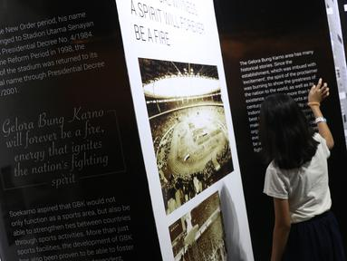 Dua orang anak melihat-lihat dokumentasi pembangunan kompleks olahraga Gelora Bung Karno yang dipamerkan di area Stadion GBK, Jakarta, Rabu (29/8). Sejumlah dokumentasi pembangunan stadion dicetak dan bisa dilihat warga. (Liputan6.com/Helmi Fithriansyah)