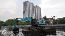 Petugas mengoperasikan eskavator untuk mengeruk lumpur di Kali Sunter Podomoro, Jakarta, Jumat (4/12). Pemprov DKI bersama Kementrian PU melakukan pembebasan bantaran sungai. (Liputan6.com/Gempur M Surya)