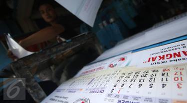 Pekerja mengerjakan pesanan pembuatan kalender di tempat produksi, kawasan Senen, Jakarta, Selasa (13/12). Menjelang pergantian tahun, pesanan kalender meningkat hingga 50% dengan harga rata-rata Rp6ribu-Rp20ribu per buah. (Liputan6.com/Immanuel Antonius)