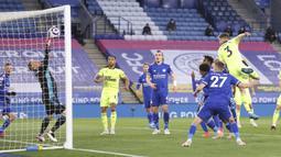 Bek Newcastle United, Paul Dummett (kanan) melepaskan sundulan yang berbuah gol kedua timnya ke gawang Leicester City dalam laga lanjutan Liga Inggris 2020/2021 pekan ke-35 di King Power Stadium, Leicester, Jumat (7/5/2021). Newcastle menang 4-2 atas Leicester. (AP/Alex Pantling/Pool)