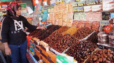 Pedagang kurma menata barang dagangannya di Pasar Tanah Abang, Jakarta, Kamis (2/5). Menjelang bulan Ramadan, permintaan buah kurma meningkat dua kali lipat dibanding hari biasa. (Liputan6.com/JohanTallo)