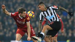 Pemain Liverpool, James Milner (kiri) berebut bola dengan pemain Newcastle United, Kenedy pada lanjutan Premier League di Anfield, Liverpool, (3/3/2018). Liverpool menang 2-0.  (AFP/Lindsey Parnaby)
