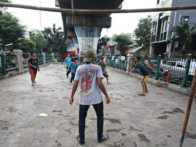 Sejumlah remaja bermain sepak bola di kolong rel kereta kawasan Juanda, Jakarta, Jumat (27/5). Tidak tersedianya ruang terbuka menyebabkan lahan tersebut dijadikan tempat bersosialisasi bagi warga. (Liputan6.com/Immanuel Antonius)