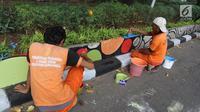Petugas PPSU Gondangdia mengecat pembatas jalan dengan warna-warni Asian Games di kawasan Menteng, Jakarta, Kamis (12/7). Cat lukisan dinding beraneka gambar dan bentuk untuk menyambut HUT kemerdekaan RI dan Asian Games 2018. (Liputan6.com/Arya Manggala)