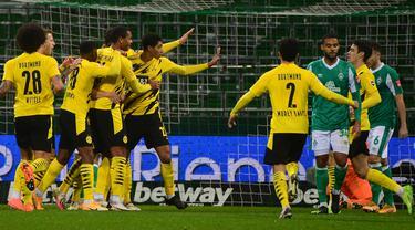 Para pemain Borussia Dortmund merayakan gol pertama yang dibuat bek Raphael Guerreiro (tengah), ke gawang Werder Bremen dalam laga lanjutan Bundesliga Liga Jerman 2020/21 pekan ke-12 di Weserstadion, Bremen, Selasa (15/12/2020). Dortmund menang 2-1 atas Bremen. (AFP/Patrik Stollarz/Pool).