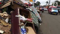 Tumpukan sampah terlihat menumpuk di sepanjang jalan pascabanjir mulai surut di kawasan Kembangan, Jakarta Barat, Minggu (5/1/2020). Nantinya sampah-sampah ini akan diangkut oleh petugas kebersihan menggunakan truk pengangkut sampah yang akan dibawa ke TPA Bantar Gebang.  (Liputan6.com/Johan Tallo)