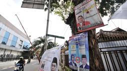 Sejumlah alat peraga kampanye (APK) calon anggota legislatif (caleg) memenuhi pepohonan yang berada di pinggir jalan, Jakarta, Rabu (20/3). Pemasangan APK caleg tersebut juga dapat merusak pepohonan serta lingkungan. (merdeka.com/Iqbal Nugroho)