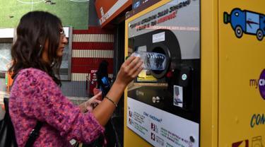 Seorang calon penumpang menukarkan sampah botol plastik dengan tiket kereta menggunakan mesin daur ulang di stasiun metro bawah tanah Cipro, Roma, Selasa (8/10/2019). (Photo by Tiziana FABI / AFP)
