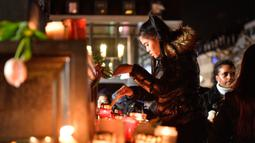 Seorang wanita menyalakan lilin saat berkabung untuk para korban penembakan brutal di Hanau, Jerman, Kamis (20/2/2020). Semua korban penembakan memiliki latar belakang imigran. (AP Photo/Martin Meissner)