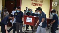 Petugas membawa peti jenazah berisi korban kecelakaan Sriwijaya Air SJ 182 atas nama Okky Bisma menuju mobil ambulans saat serah terima kepada pihak keluarga di RS Polri, Jakarta, Kamis (14/1/2021). Okky Bisma menjadi korban pertama yang berhasil teridentifikasi. (merdeka.com/Imam Buhori)