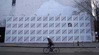 Seorang pengendara sepeda melewati tembok besar yang dimural oleh seniman Banksy di wilayah Manhattan, New York (15/3). Secara keseluruhan mural ini menggambarkan sosok Zehra Dogan yang berada di balik jeruji besi. (AFP Photo/Timothy A. Kliit)