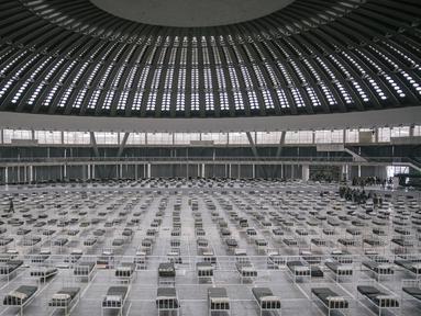 Tentara Serbia menyiapkan tempat tidur di dalam aula Belgrade Fair yang diubah menjadi rumah sakit sementara virus Corona, Selasa (24/3/2020). Rumah sakit tersebut direncanakan menampung 3000 tempat tidur untuk  menangani pasien dengan gejala ringan corona Covid-19. (Vladimir Zivojinovic/AFP)