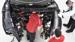 Mekanik melakukan pemasangan instalasi listrik mobil Porsche Taycan saat proses perakitan di pabrik perusahaan Porsche AG di Stuttgart, Jerman, Rabu (4/3/2020). Porsche Taycan merupakan mobil bertenaga listrik pertama  dari pembuat mobil mewah Jerman, Porsche AG. (AFP Photo/Thomas Kienzie)
