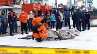 Petugas KPLP dan Basarnas memeriksa barang temuan yang diduga serpihan pesawat Sriwijaya Air SJ 182 di Dermaga JICT 2, Jakarta, Minggu (10/1/2021). Sriwijaya Air SJ 182 hilang kontak empat menit usai lepas landas dari Bandara Soetta. (Liputan6.com/Helmi Fithriansyah)