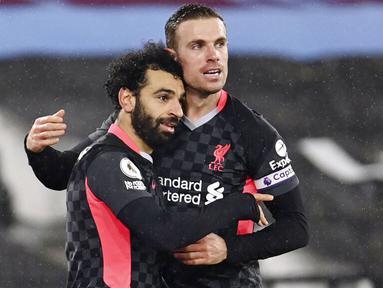 Penyerang Liverpool, Mohamed Salah, melakukan selebrasi bersama Jordan Henderson usai mencetak gol ke gawang West Ham United pada laga Liga Inggris di Stadion London, Minggu (31/1/2021). Liverpool menang dengan skor 3-1. (Justin Setterfield/Pool via AP)
