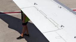 Kru American Airlines berlindung dari cuaca panas dengan berteduh di bawah sayap pesawat terbang di Bandara Internasional Sky Harbor, Phoenix, Amerika Serikat, Rabu (25/7). Phoenix mencapai rekor suhu tinggi pada Senin dan Rabu sore. (AP Photo/Matt York)