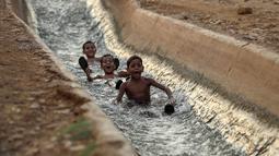 Anak-anak bermain di aliran mata air yang digunakan untuk irigasi untuk mendinginkan tubuh saat suhu udara mencapai 44 derajat Celcius di kota Jericho, Tepi Barat (1/9/2020). (AFP Photo/Ahmad Gharabli)