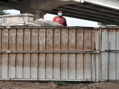 Warga berada di balik pagar pembatas yang menutup akses menuju kawasan Cipinang Melayu, Jakarta, Minggu (29/3/2020). Warga membatasi aktivitas pengunjung yang melintasi kawasan mereka dengan menutup sebagian jalan dengan seng guna mengantisipasi penyebaran corona Covid-19 (merdeka.com/Iqbal Nugroho)