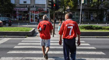Dua pria mengenakan jersey legenda Manchester United David Beckham jelang pertandingan final UEFA Super Cup antara Real Madrid melawan MU di Philip II Arena di Skopje, Macedonia, (7 /8). (AFP Photo/Armend Nimani)