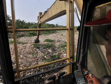 Petugas dari Dinas Lingkungan Hidup Kabupaten Bekasi menggunakan kendaraan alat berat mengeruk sampah yang memenuhi Kali Pisang Batu, Tarumajaya, Bekasi, Jawa Barat, Rabu (9/1). (Merdeka.com/Iqbal S. Nugroho)
