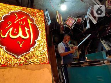Pengrajin tengah mebuat bingkai untuk lukisan kaligrafi di Tangerang, Rabu (6/5/2020). Akibat Covid-19 yang tengah mewabah membuat para pengrajin tersebut terimbas akibat sepinya peminta lukisan kaligrafi pada bulan ramadan tahun ini. (Liputan6.com/Angga Yuniar)