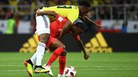 Bek timnas Kolombia, Yerry Mina berebut bola dengan pemain Inggris, Raheem Sterling pada babak 16 besar Piala Dunia 2018 di Stadion Spartak, Selasa (3/7). Selain adu penalti, sebuah kejadian menarik tertangkap kamera pada laga itu. (AFP/FRANCK FIFE)
