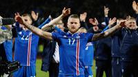 Kapten timnas Islandia, Aron Gunnarsson merayakan kemenangan timnya atas Kosovo pada laga Grup I Kualifikasi Piala Dunia 2018 di Laugardalsvollur, Senin (9/10). Menang 2-0, Islandia pertama kalinya tampil dalam gelaran Piala Dunia. (AP/Brynjar Gunnarsson)