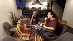 Nadia Chaouch (depan) berbuka puasa dengan suaminya, Ahmad Kamel, dan anak mereka, Yusuf Kamel di rumah mereka selama wabah virus corona dirumahnya di Seattle (28/4/2020). (AP/Elaine Thompson)