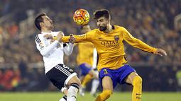 Striker Valencia, Paco Alcacer, berebut bola dengan bek Barcelona, Gerard Pique, pada laga La Liga Spanyol di Stadion Mestalla, Spanyol, Sabtu (5/12/2015). (EPA/Kai Foersterling)