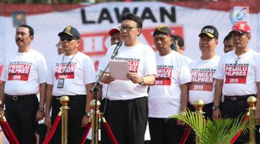 Mendagri, Tjahjo Kumolo (tengah) membaca ikrar lawan kampanye hoax dan berujar kebencian saat apel bersama ASN Kemendagri dan BNPP di Lapangan Monas, Jakarta, Jumat (15/2). Apel diikuti ASN dari kedua instansi tersebut. (Liputan6.com/Helmi Fithriansyah)