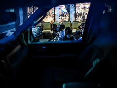 Pria Muslim terlihat melalui jendela mobil saat mereka salat di trotoar di luar restoran selama bulan suci Ramadhan di Lauderhill, Florida, Jumat (30/4/2021). Selama puasa Ramadhan, umat Islam tidak makan, minum, atau aktivitas seksual dari fajar hingga matahari terbenam. (CHANDAN KHANNA/AFP)