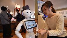 Seorang karyawati dari restoran sushi Hamazushi menguji coba robot humaoid Pepper saat press preview di Saitama, Jepang (2/2). Robot tersebut merupakan buatan dari perusahaan telekomunikasi raksasa Jepang yang bernama Softbank. (AFP/Kazuhiro Nogi)