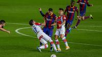 Pemain Barcelona Lionel Messi memperebutkan bola dengan pemain Alaves Adrian Marin pada pertandingan Liga Spanyol di stadion Camp Nou di Barcelona, Spanyol, Sabtu, 13 Februari 2021. (Foto AP / Joan Monfort)