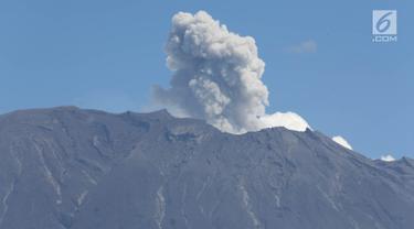 Gunung Agung erupsi mengembuskan asap bercampur abu vulkanik terlihat dari kawasan Sidemen, Karangasem, Bali, Jumat (8/12). Erupsi magmatik tersebut berembus hingga ketinggian 2.100 meter di atas puncak kawah. (Liputan6.com/Immanuel Antonius)