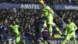 Striker Levante, Emmanuel Boateng, duel udara dengan bek Barcelona, Thomas Vermaelen, pada laga La Liga di Stadion Ciutat de Valencia, Valencia, Minggu (16/12). Levante kalah 0-5 dari Barcelona. (AFP/Jose Jordan)