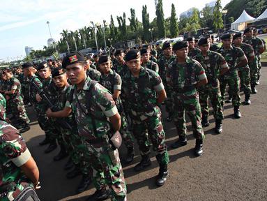 Petugas TNI mengikuti apel gabungan di Monas, Jakarta, Kamis (31/12). Sebanyak 1300 personel gabungan yang terdiri dari polisi, TNI, Pol PP, dan Pramuka dikerahkan untuk mengamankan perayaan malam tahun baru. (Liputan6.com/Immanuel Antonius)