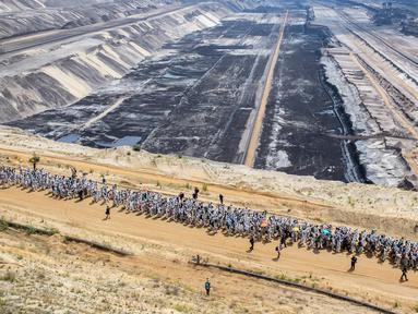 Aktivis iklim berjalan mamasuki tambang batu bara lignit Garzweiler di Garzweiler, Jerman barat, Sabtu (22/6/2019). Ratusan aktivis iklim menduduki tambang batu bara yang dijalankan oleh raksasa energi RWE. (Marcel Kusch/DPA/AFP)